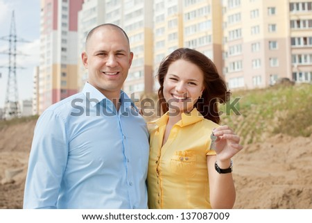 Happy couple with key against new brick house - stock photo