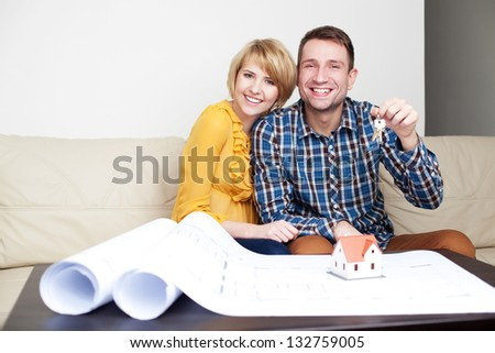 Happy couple with keys to new home - stock photo