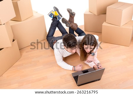 Happy couple with laptop and boxes moving into new home apartment  - stock photo