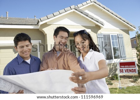 Happy couple with real estate agent reviewing blueprint in front of new house - stock photo