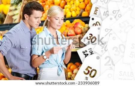Happy couple with sale coupons decides what to buy - stock photo