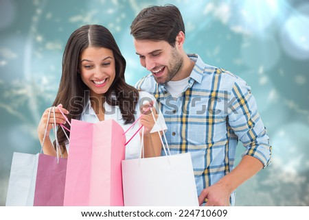 Happy couple with shopping bags against blurred christmas background - stock photo