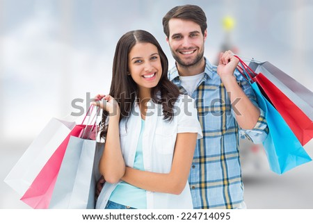 Happy couple with shopping bags against blurry christmas tree in room - stock photo