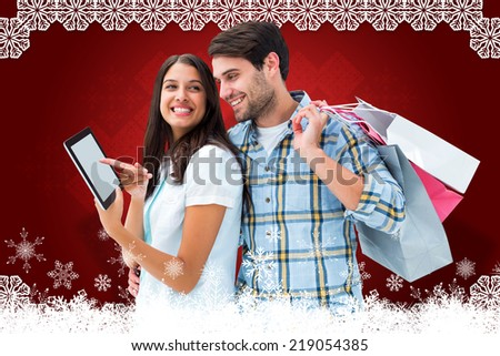 Happy couple with shopping bags against christmas themed snow flake frame - stock photo