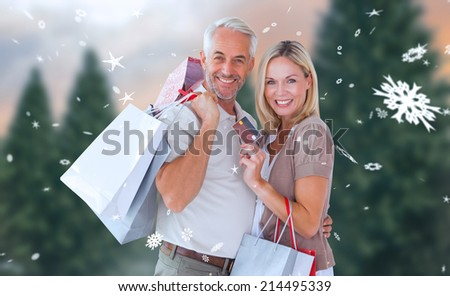 Happy couple with shopping bags and credit card against fir tree forest - stock photo