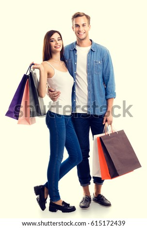 Happy couple with shopping bags, standing close to each other and looking at camera with smile. Caucasian models in love, holiday sales, shop, retail, consumer concept.