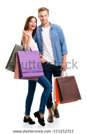 Happy couple with shopping bags, standing close to each other with smile. Caucasian models in love, holiday sales, shop, retail, consumer concept, isolated on white background.