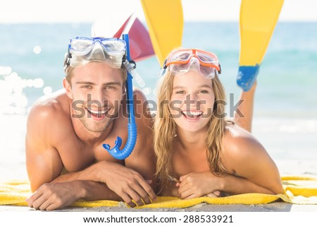 Happy couple with snorkel and flippers at the beach - stock photo