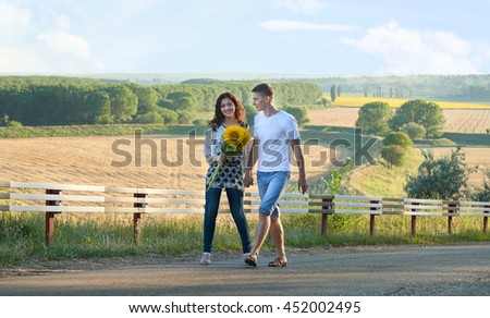 happy couple with sunflowers having fun and walking along country road outdoors - romantic travel, hiking, tourism and people concept - stock photo