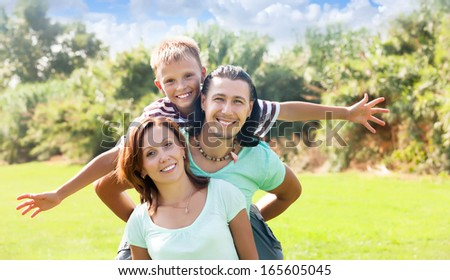 Happy couple with teenage son  enjoying time in sunny park