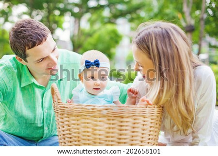 Happy couple with their baby in a laundry basket - stock photo