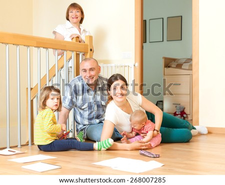 Happy couple with their offspring and grandmother sitting togetjer on floor at home in living room  - stock photo