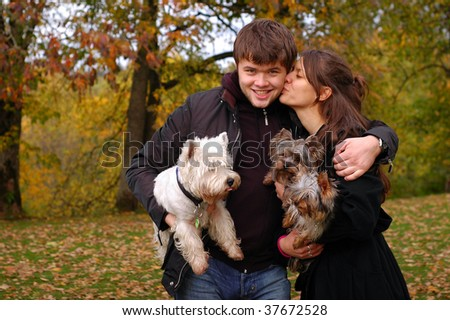 Happy couple with their three dogs - stock photo