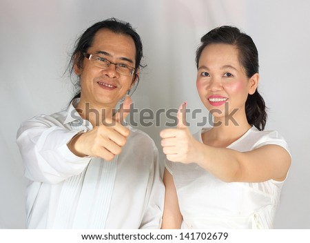 happy couple with thumbs-up - stock photo