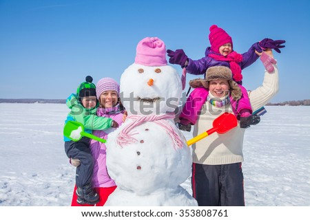 Happy couple with two children making big snowman