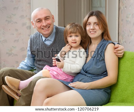 Happy couple with 2 year child in home interior