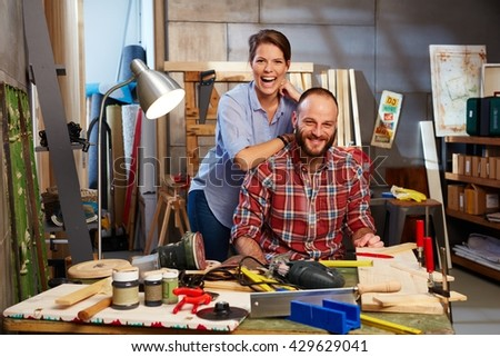 Happy couple working in workshop, smiling, looking at camera.