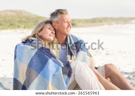 Happy couple wrapped up in blanket at the beach - stock photo