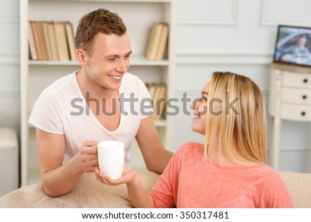 Happy couple. Young couple looks happy while sitting on the sofa and drinking tea.  - stock photo