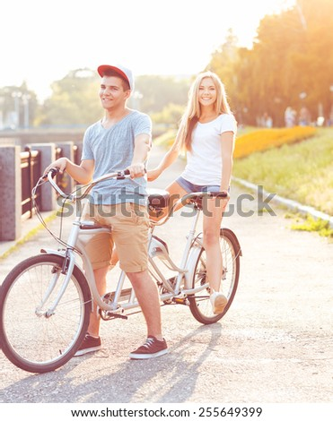 Happy couple - young man and woman riding a bicycle in the park outdoors - stock photo
