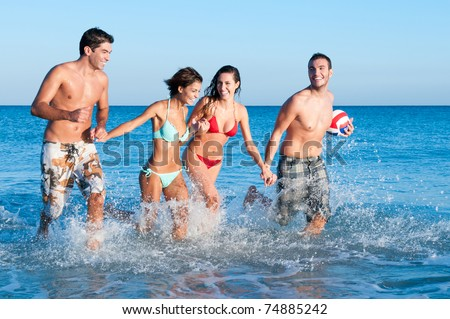 Happy couples of friends playing together and running in the water - stock photo