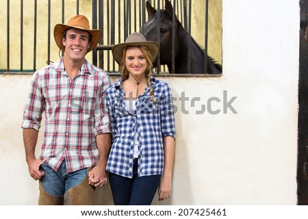 happy cowboy and cowgirl couple holding hands inside stables - stock photo