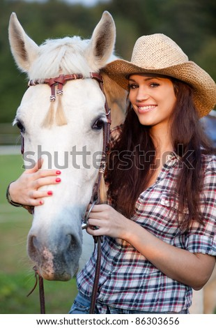 Happy cowgirl with her white horse. Selective focus. - stock photo