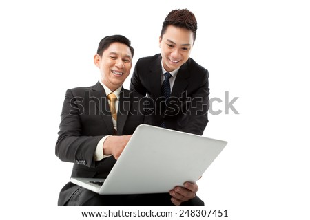 Happy coworkers looking at the laptop screen