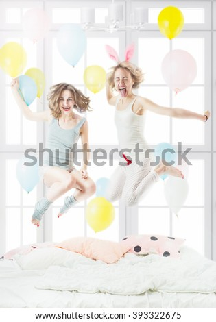 Happy crazy two friends girl, Jumping having fun pijamas party on the bed. Sunny light room with . Active emotional woman