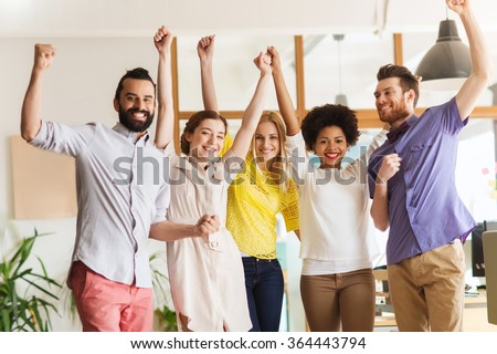 happy creative team celebrating victory in office