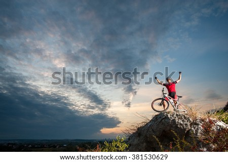 Happy cross country biker celebrates his success on the top of the mountain, enjoying beautiful sunset on overview point in the evening - stock photo