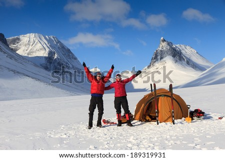 Happy cross country skiers at their tent during a winter trekking in the mountains of Lapland. - stock photo