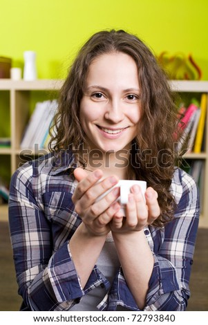 Happy curly student holding a cup - stock photo