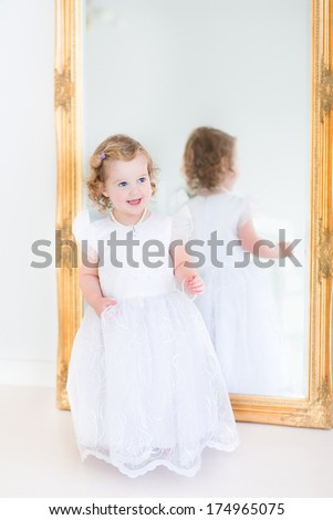 Happy curly toddler girl trying on a beautiful white dress in front of a big mirror - stock photo