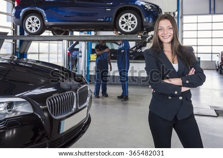 Happy customer in garage with her repaired car in the background - stock photo