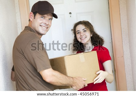 Happy customer receiving a package from a delivery man.  Focus on girl. - stock photo