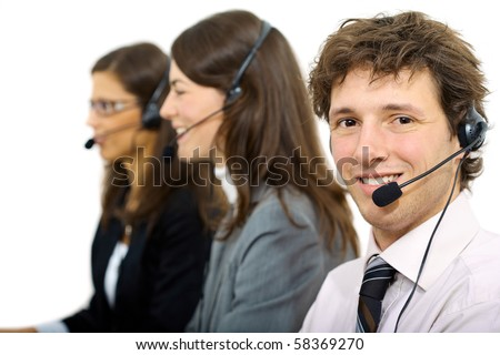 Happy customer service representatives sitting in a row and talking on headset, smiling. Isolated on white background. - stock photo