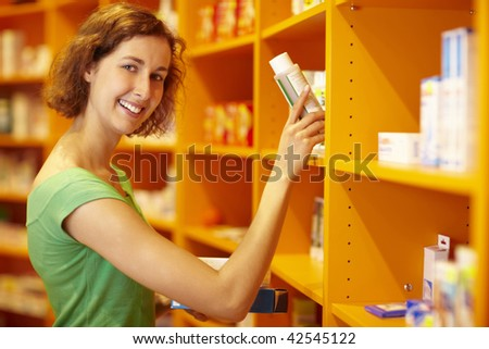 Happy customer taking medicine from a shelf - stock photo