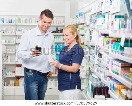 Happy Customer Using Mobile Phone While Pharmacist Holding Produ - stock photo