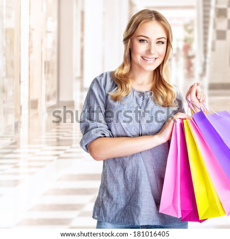 Happy customer with colorful paper bag in great mall, attractive girl enjoying shopping, buying gifts, spending money concept - stock photo