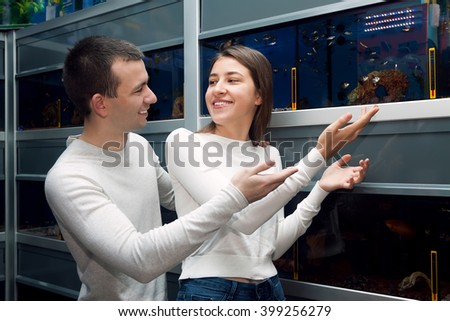happy customers selecting tropical fish in aquarium tank - stock photo