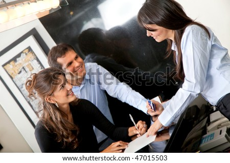 Happy custumers paying at the hotel with a credit card - stock photo