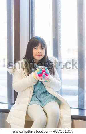 Happy cute asian girl holding glass in hand at train station toyama japan. - stock photo