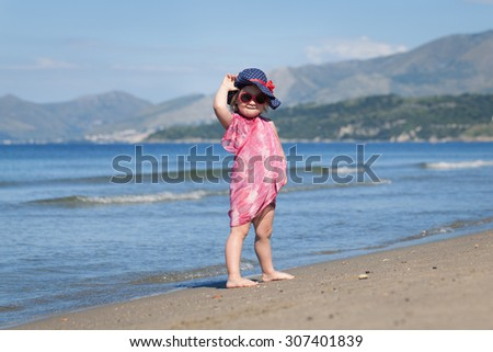 Happy cute baby girl in hat and sunglasses, walking near sea