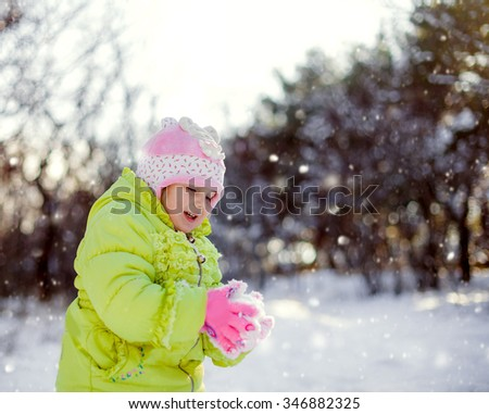 Happy cute baby girl in winter park - stock photo
