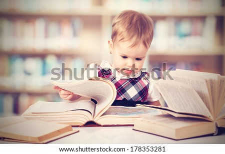 Happy cute baby girl reading a book in a library