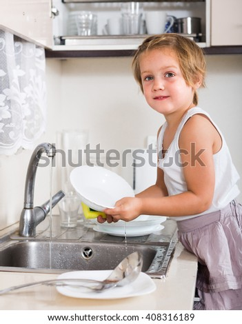 Happy cute baby girl washing dishes at home kitchen