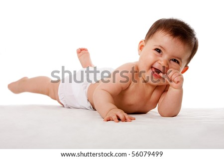 Happy cute baby laying with thumb in mouth, isolated.