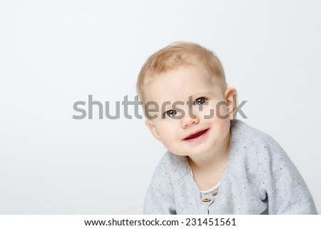 happy cute baby looking into the camera. The baby sitting  over white background
