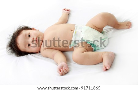 happy cute baby lying on the bed - stock photo